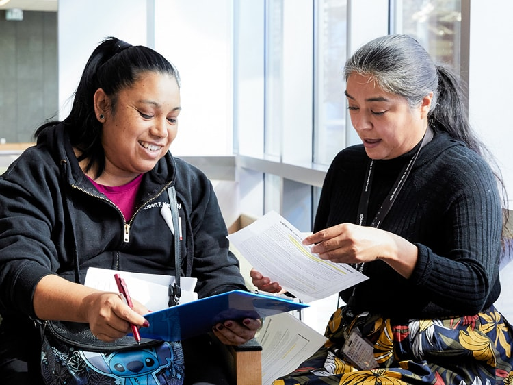 Two women look over paperwork in hospital waiting room