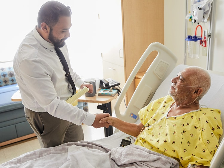 Doctor greets older man sitting up in hospital bed