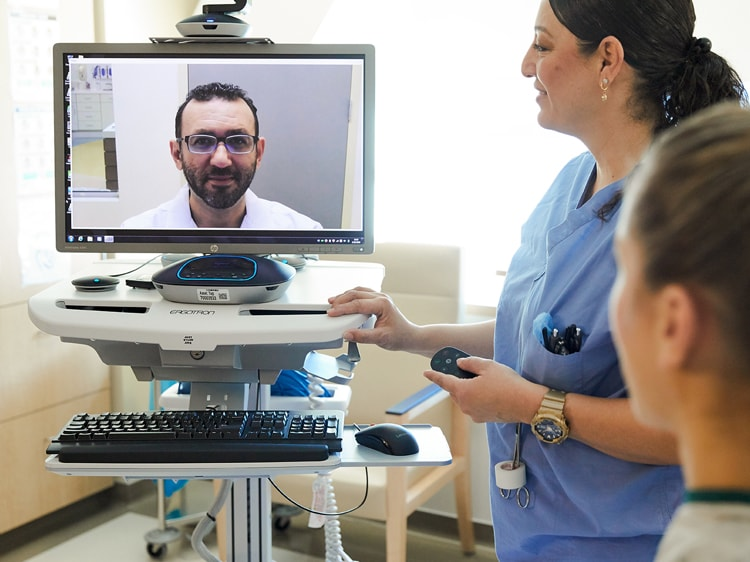 Nurses interact with a remote physician using a telemedicine device