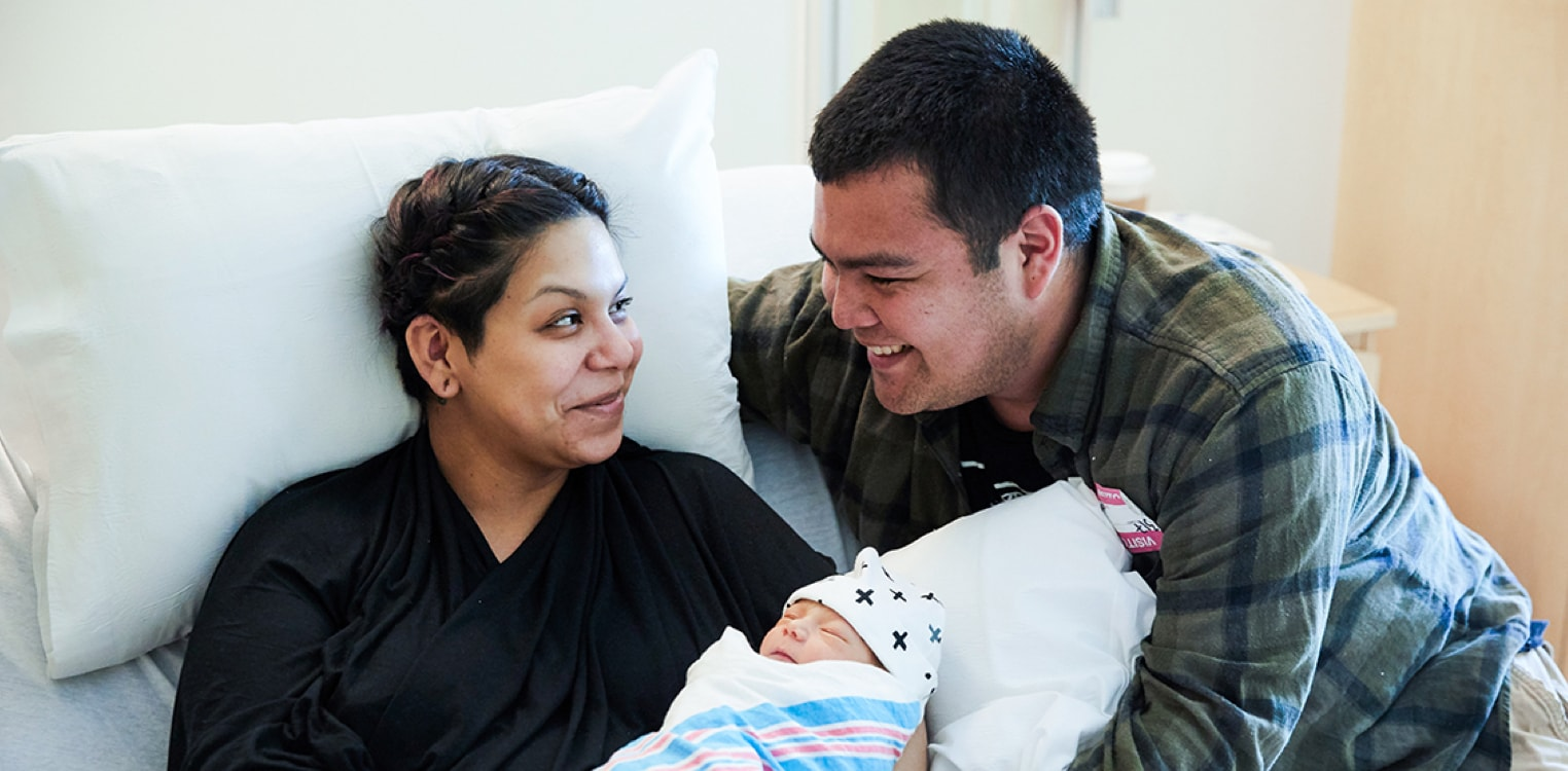 New Latino parents smile while holding their newborn baby
