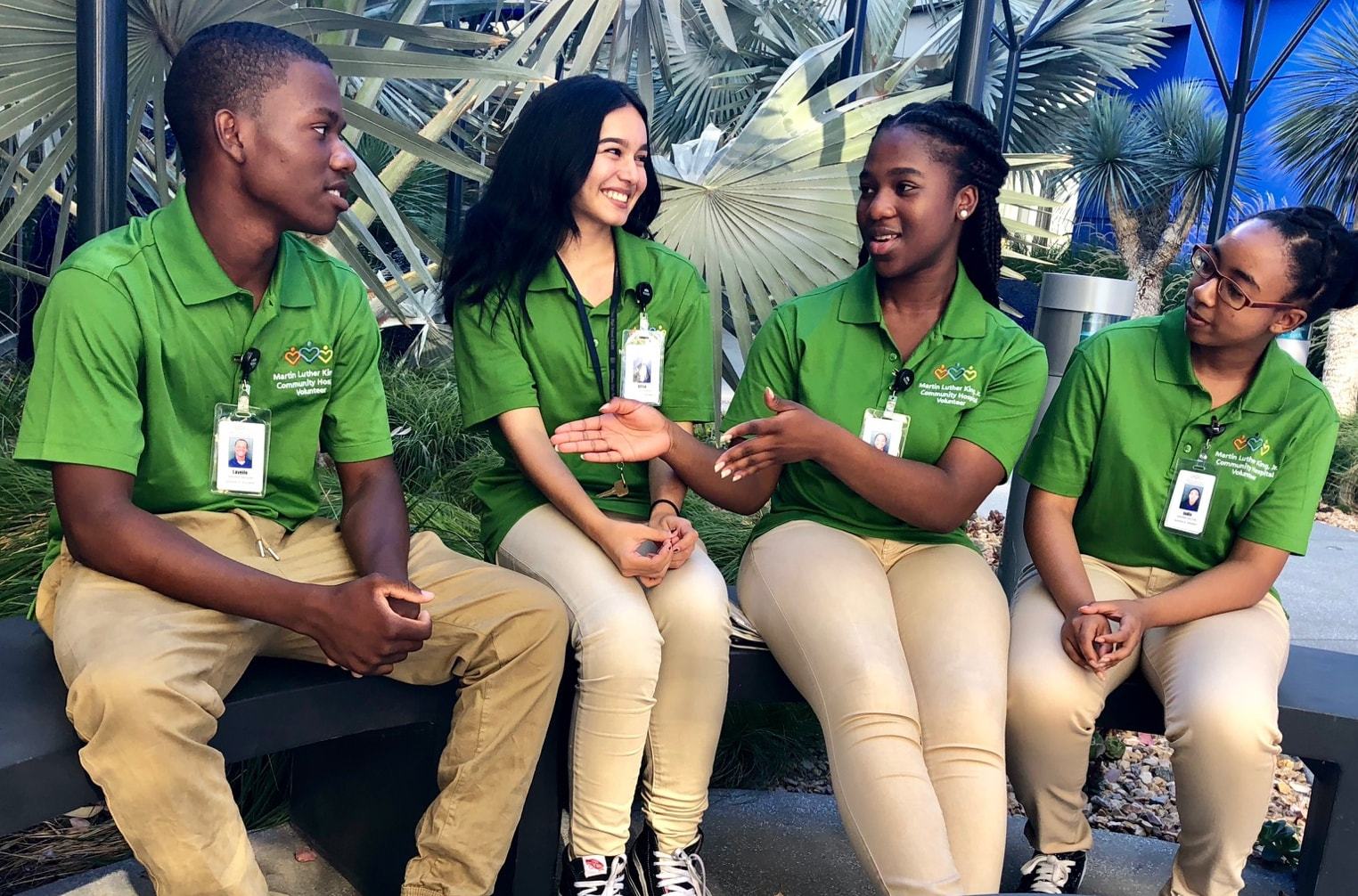 Four high school volunteers wearing green t-shirts sitting next to each other talking