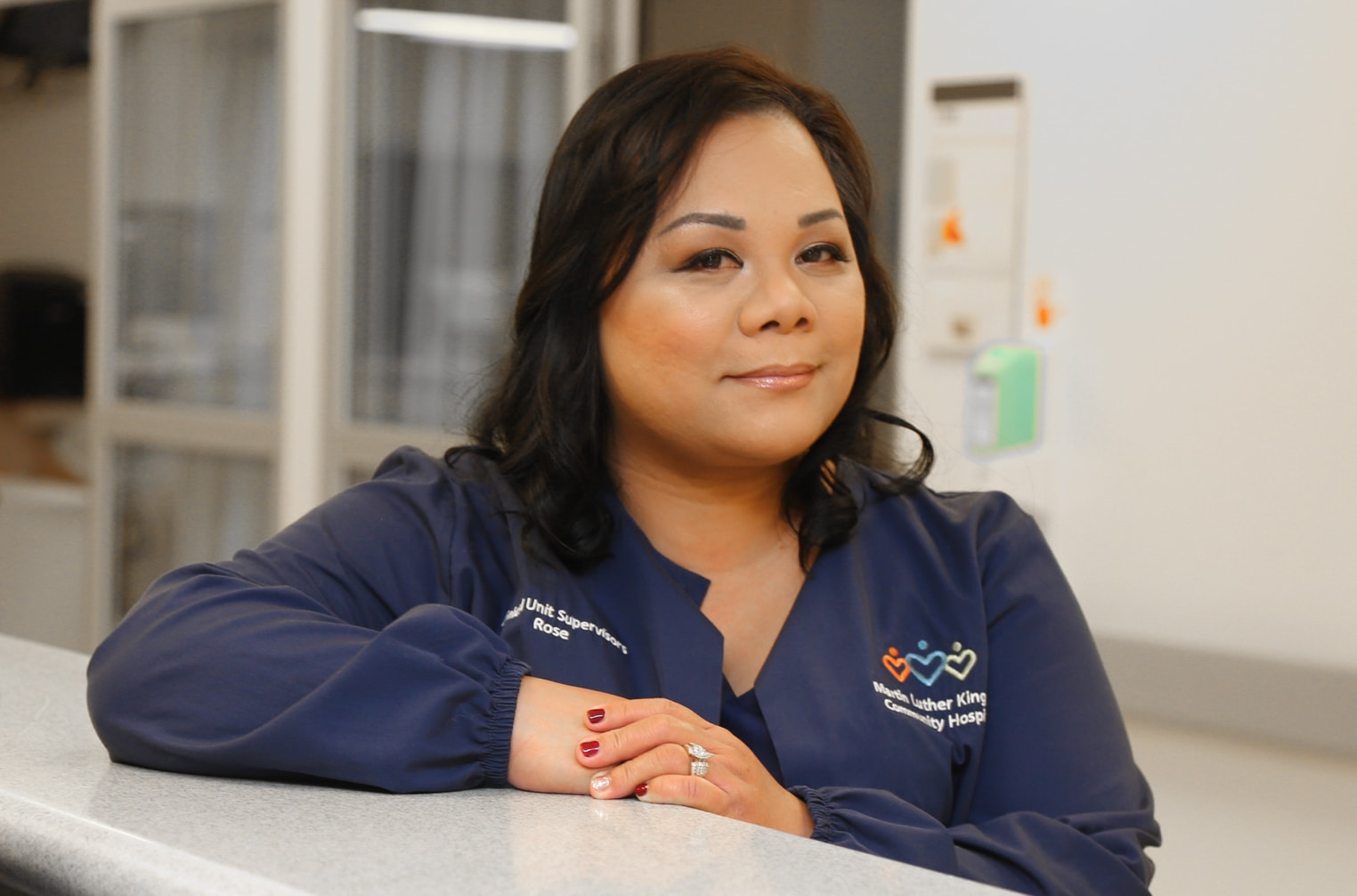 Smiling ICU Nursing Supervisor Lyrose Ortiz standing at nurse's station