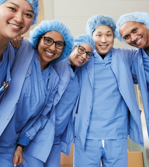 A group of smiling nurses in scrubs