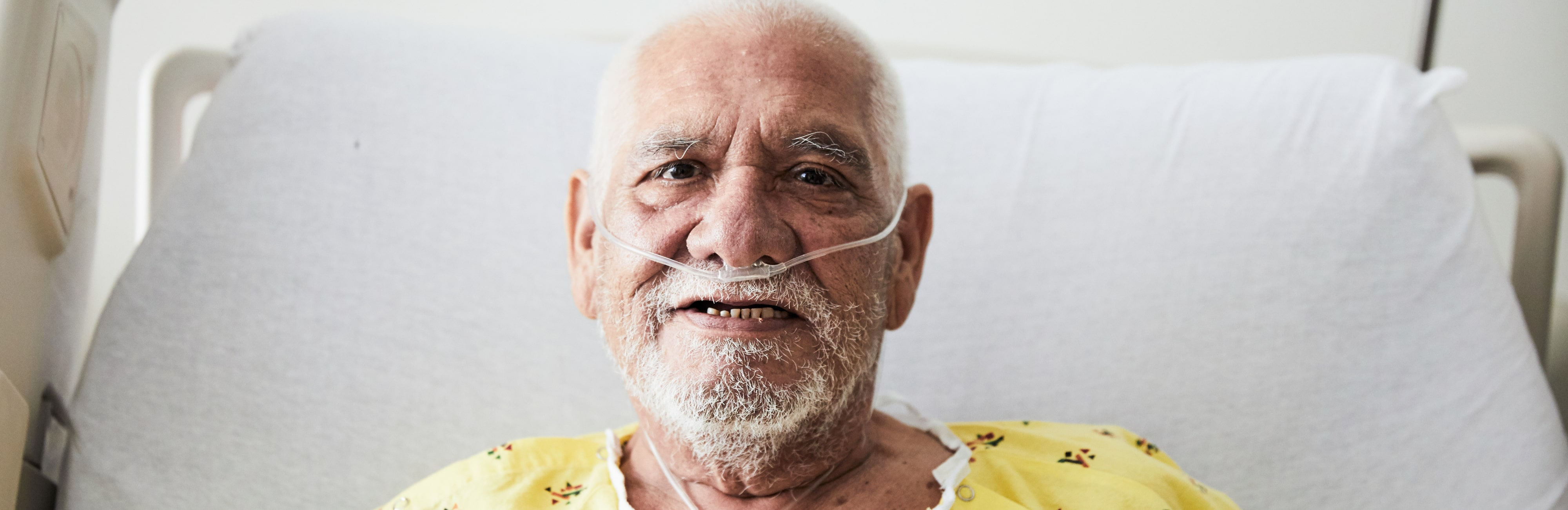 Elderly man smiling and sitting in a hospital bed
