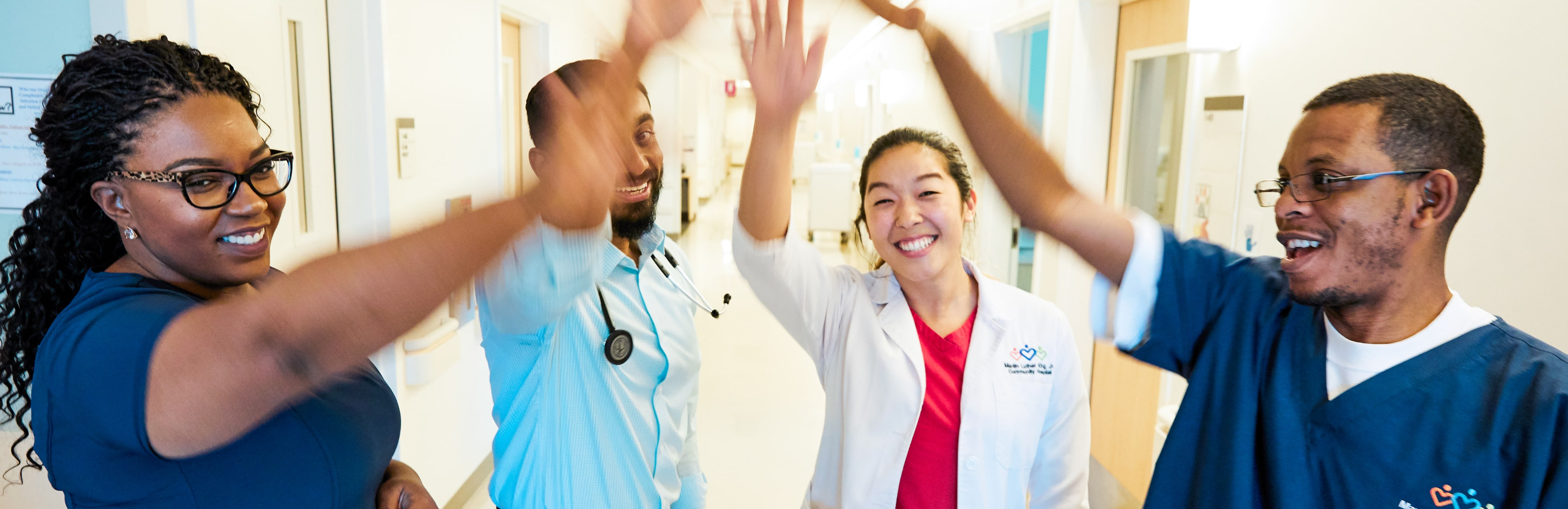 Two nurses and two physicians smiling and cheering