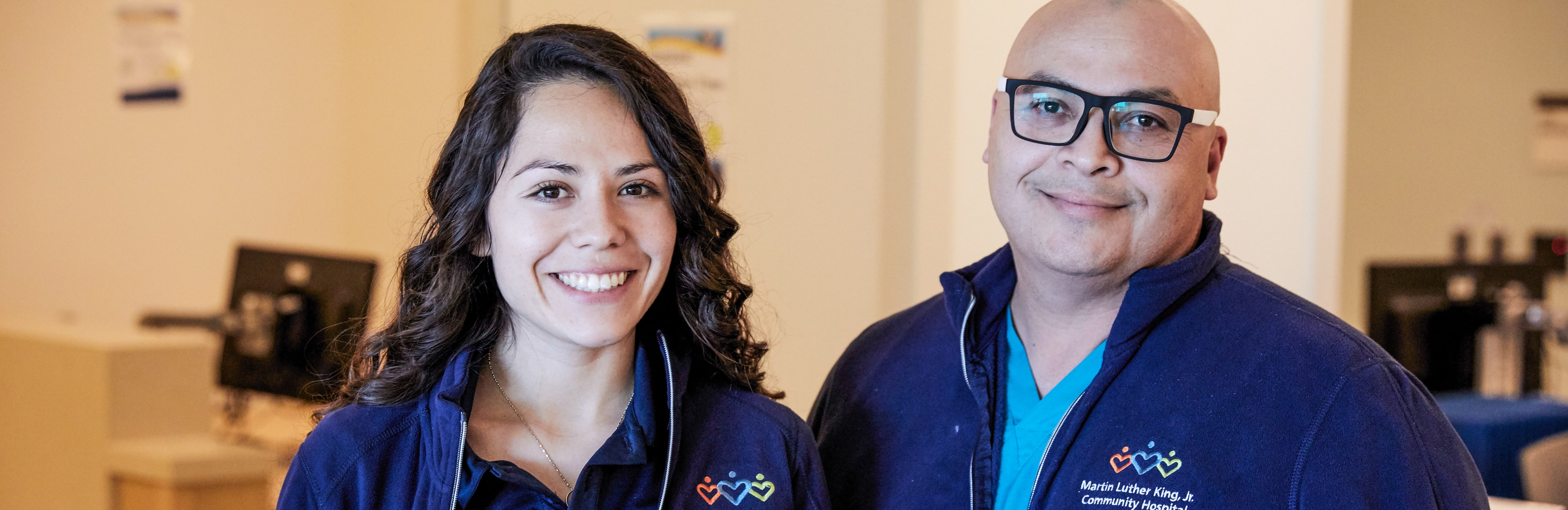 Two Latino hospital volunteers smiling